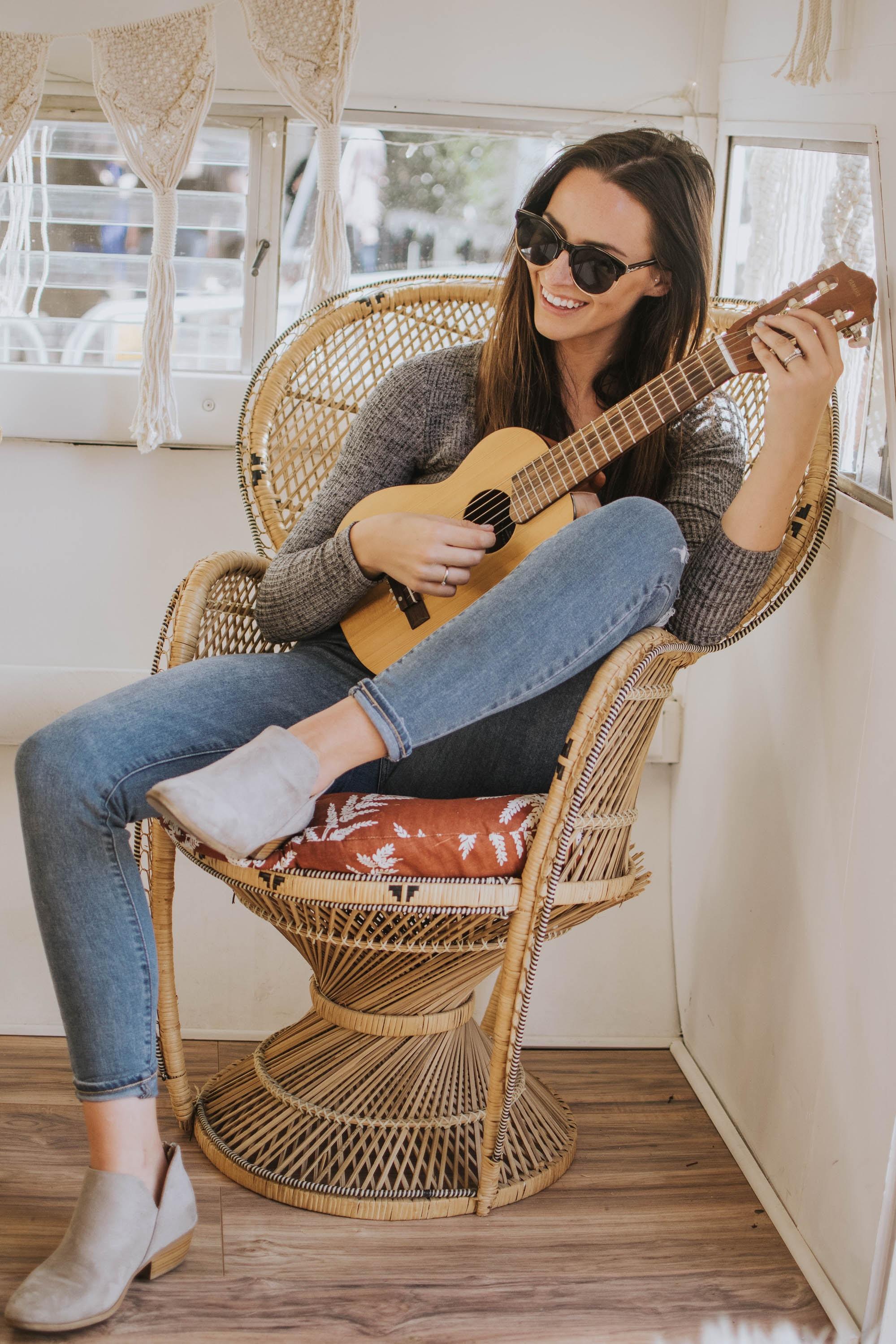 женщина на плетеном стуле с гитарой